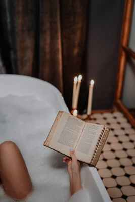 person reading book on white bathtub